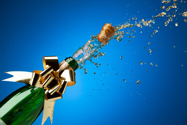 Cork popping from Champagne bottle with splashes