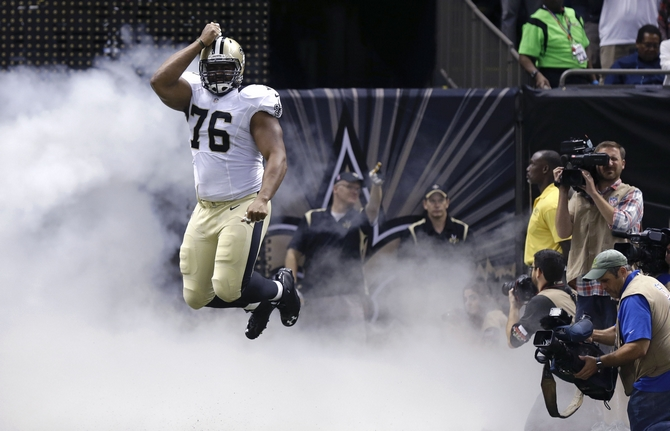 New Orleans Saints defensive end Akiem Hicks (76) leaps into the air as he runs onto the field before an NFL preseason football game in New Orleans, Sunday, Aug. 30, 2015. (AP Photo/Brynn Anderson) ORG XMIT: NYOTK