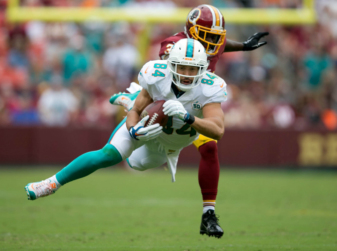 Miami Dolphins tight end Jordan Cameron (84) makes a leaping catch in front of Washington Redskins free safety Trenton Robinson (34) at FedExField in Landover, Maryland on September 13, 2015.  (Allen Eyestone / The Palm Beach Post)