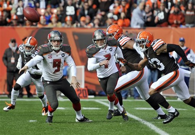 Tampa Bay Buccaneers punter Michael Koenen (9), kicker Patrick Murray race Cleveland Browns cornerback Joe Haden to the ball after a blocked field goal attempt in the first quarter of an NFL football game, Sunday, Nov. 2, 2014, in Cleveland. (AP Photo/David Richard)