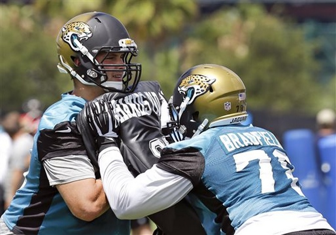 Jacksonville Jaguars offensive tackle Luke Joeckel, left, and tackle Cameron Bradfield (78) perform a drill during NFL football minicamp in Jacksonville, Fla., Wednesday, June 18, 2014. (AP Photo/John Raoux)