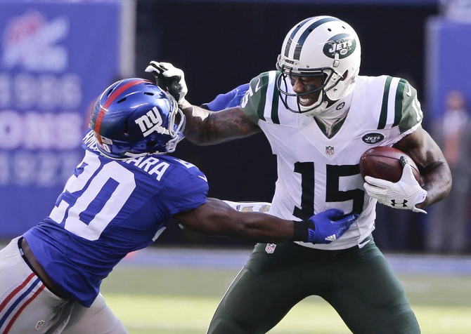 New York Jets wide receiver Brandon Marshall (15) stiff-arms New York Giants' Prince Amukamara during the first half of an NFL football game Sunday, Dec. 6, 2015, in East Rutherford, N.J. (AP Photo/Julie Jacobson)